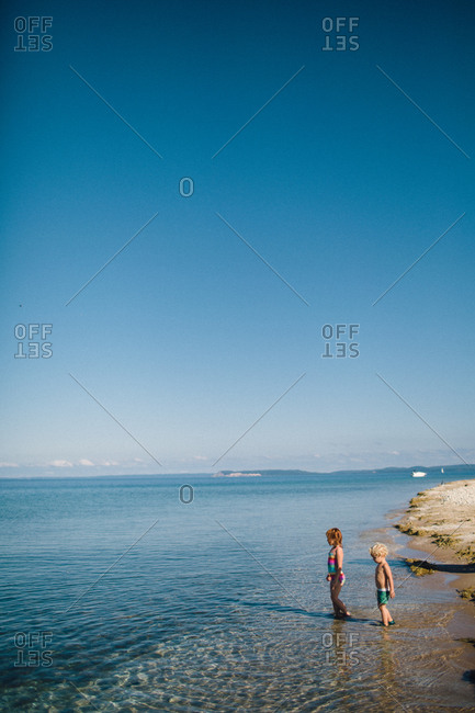 Little girl and her brother wading into the water