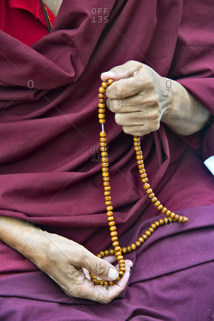 Detail of Buddhist monk holding prayer beads at the Mahabodhi Temple Complex in Bodh Gaya, India