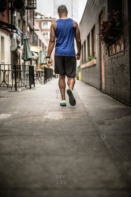 Young man walking down an alley before a jog, Seattle, Washington