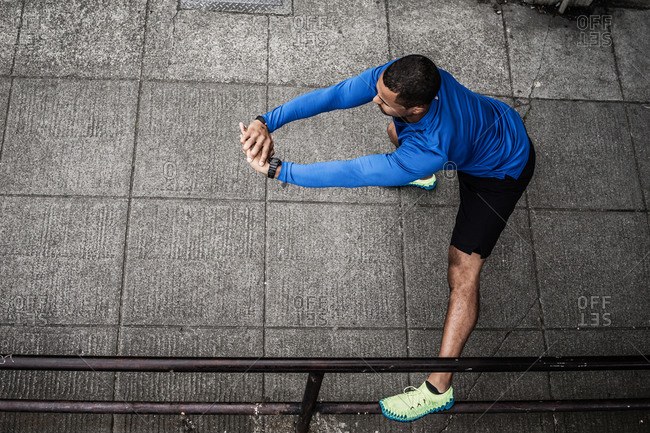 Young man stretching on the sidewalk, Seattle, Washington