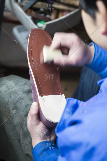 Shoemaker painting a shoe sole