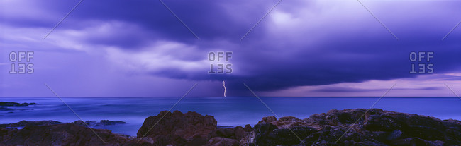 A single bolt of lightening hits the ocean in a panorama of a rocky coast