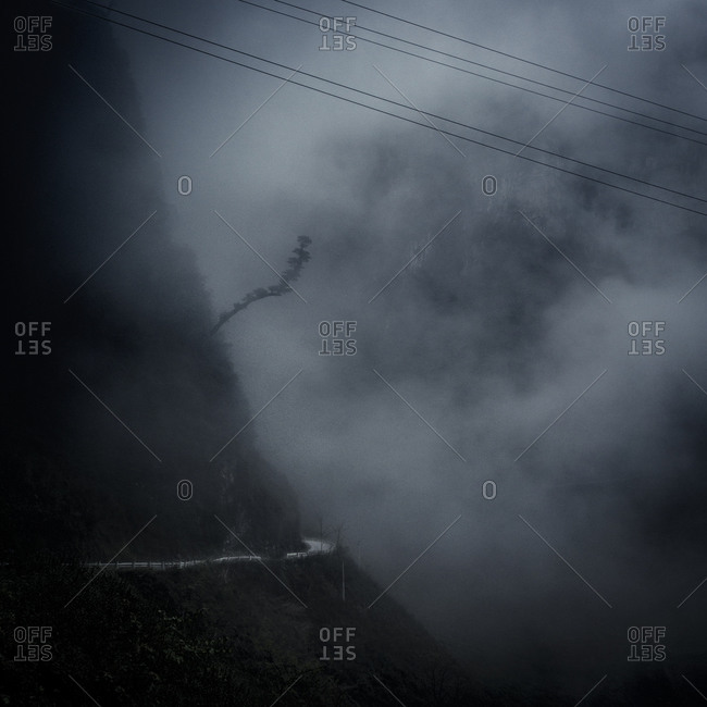 A mountain road is covered by mist