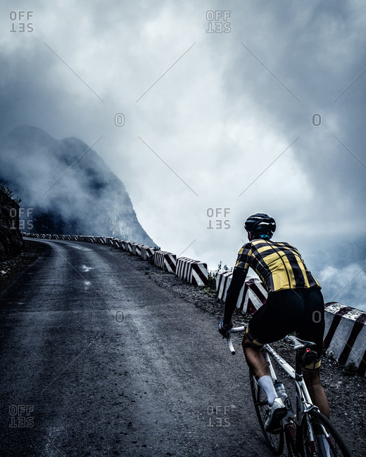 A bike rider travels up a mountain road