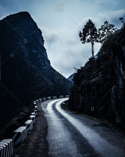 A road bending around hills at dusk