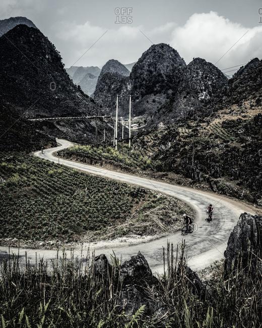 Bike riders travel along a flat road