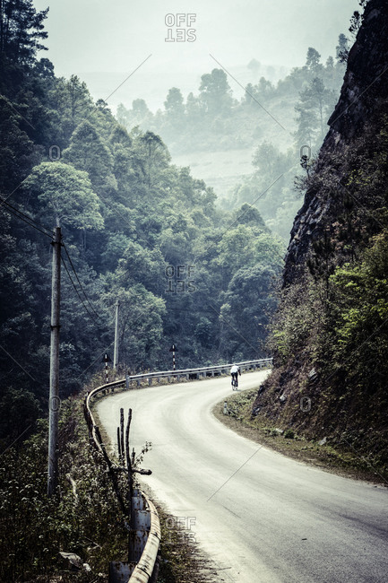 A bike rider traveling along a mountain road