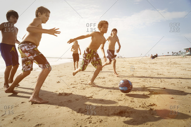 Group of boys playing soccer on the beach