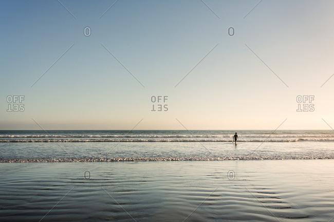 A lone beachgoer walks in shallow waters of a beach