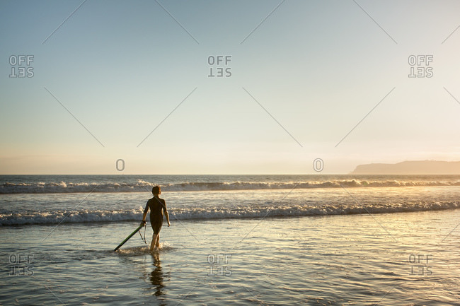 A boy drags a stick wading in the shallow waters of a beach