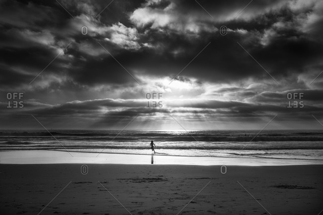 Rays of sun backlight a child running along the tide waters of a beach