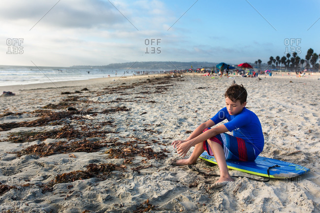 A boy sits on his body board on the sands of a beach