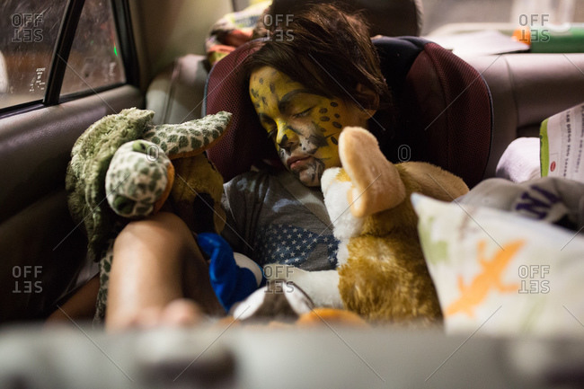 A girl with tiger face paint sleeps in her car seat surrounded by stuffed animals