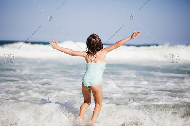 A young girl plays in the waves of the ocean, New South Wales Australia