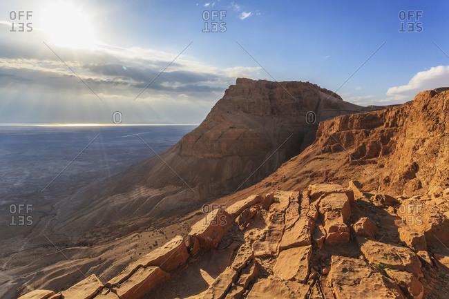 Rugged terrain and sunbeams at sunrise, Masada, Israel
