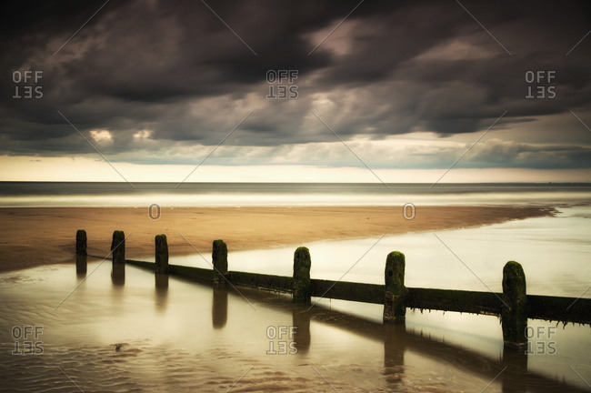 A fence submerged in the water at the coast with storm clouds overhead, Berwick, Northumberland