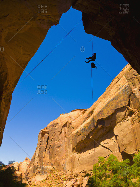 A female athlete rappelling down a dry Utah Slot Canyon waterfall