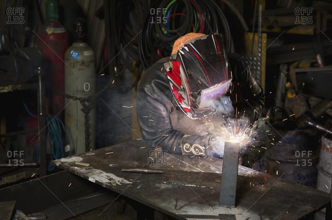 Female welder welding in a shop