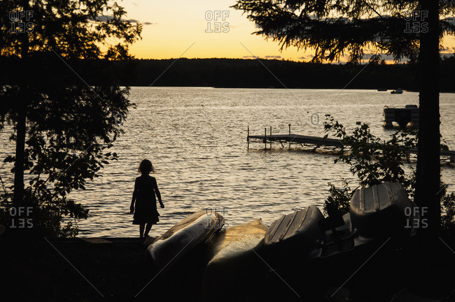 A young girl watches a sunset on a summer's evening