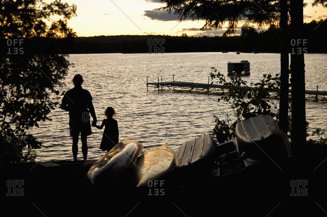 Father and daughter watch a sunset on a summer\'s evening