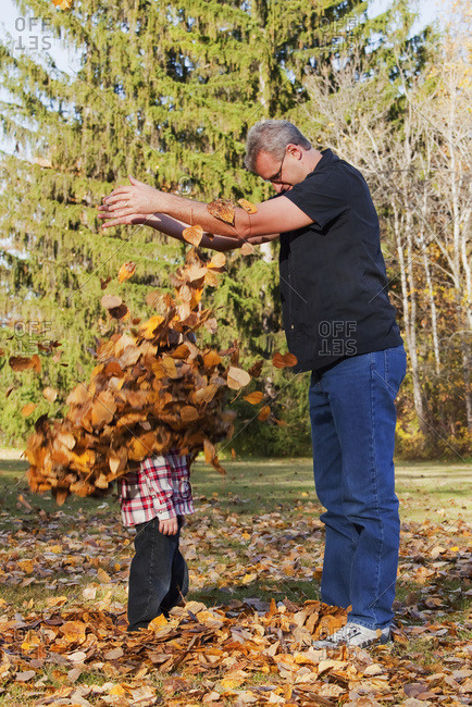 Grandfather and grandson playing in the leaves in a park in autumn