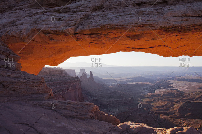 The lower arch glows a brilliant orange as the sun rises over Mesa arch in Canyonlands National Park