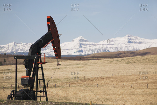 Pumpjack in a field with snow covered mountains and blue sky, Alberta