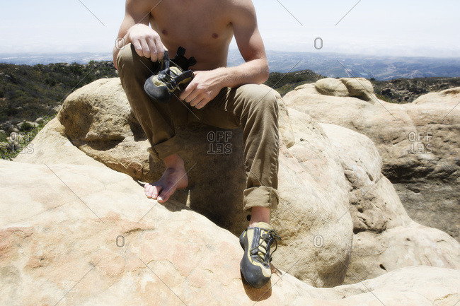 Man putting on his rock climbing shoes at the top of lizard's mouth