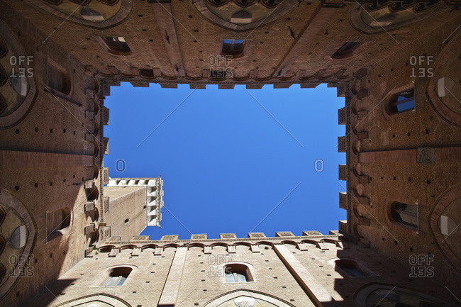 Low angle view up the walls of a building to a blue sky, Siena, Italy