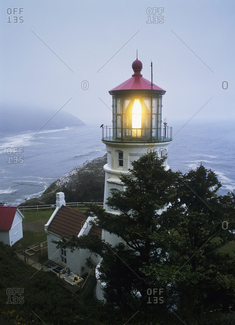 The Heceta Head Lighthouse flashes on a foggy morning, Oregon