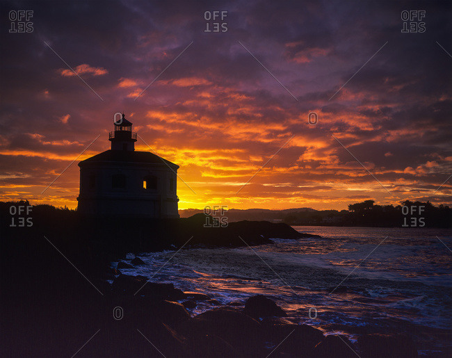 The sun rises behind the Coquille River Lighthouse, Oregon