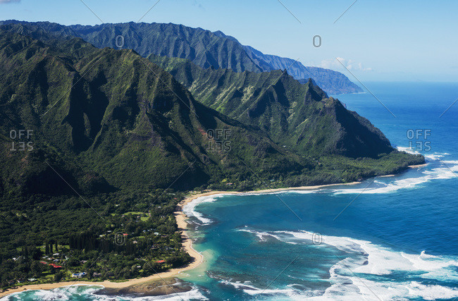 Rugged mountains along the coastline and the surf meets the beach, Haena, Hawaii