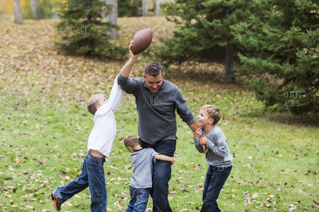 A father playing football with his sons in a park in autumn