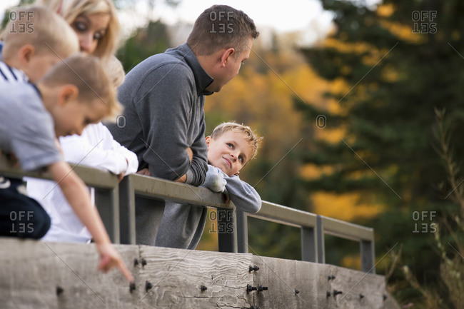 Young family on a bridge in a park in autumn