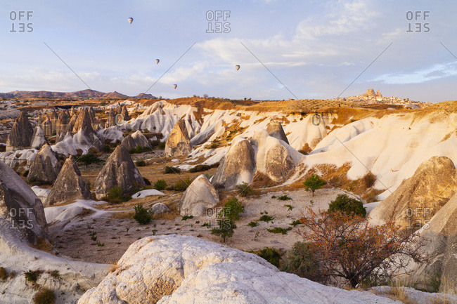 Hot air balloons over a landscape of rugged rock formations and cliffs, Goreme, Cappadocia, Turkey
