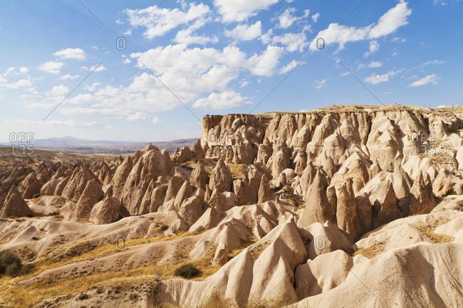 Fairy chimneys and cliffs in a rugged, barren landscape in Deverent Valley, Cappadocia, Turkey