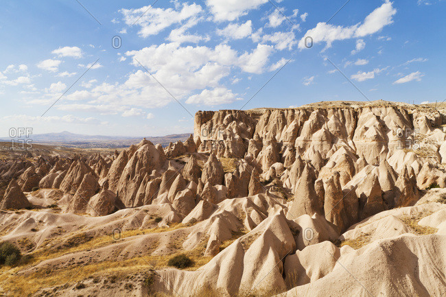 Fairy chimneys and cliffs in a rugged, barren landscape in Deverent Valley, Cappadocia, Turkey