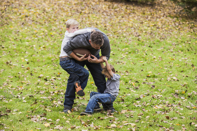 A father playing football with his boys in a park