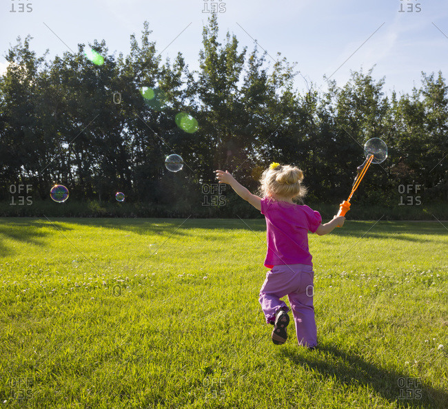 Young girl running in a park making bubbles