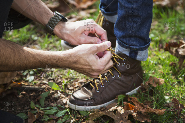 Father tying his son\'s hiking boots in a park
