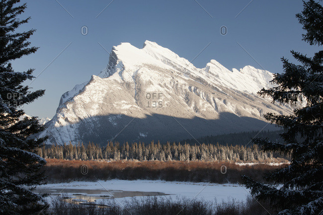 Snow covered mountain framed by silhouetted evergreen trees with snow covered lake and blue sky, Banff, Alberta,