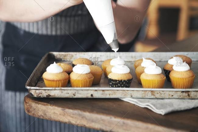 Small homemade cupcakes being frosted