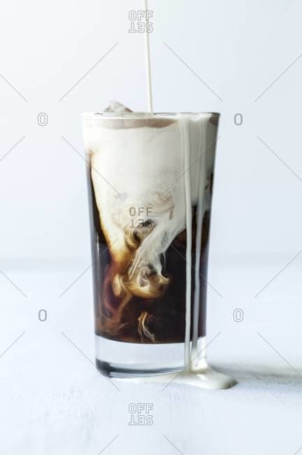 Cream poured into a clear glass of iced coffee