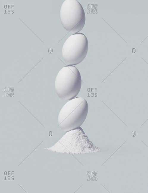 Four eggs stacked on a pile of powder on a white background