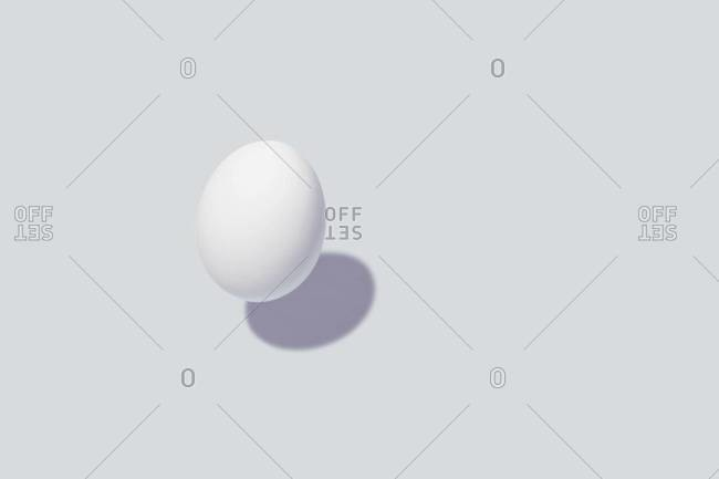 An egg floating over a white background