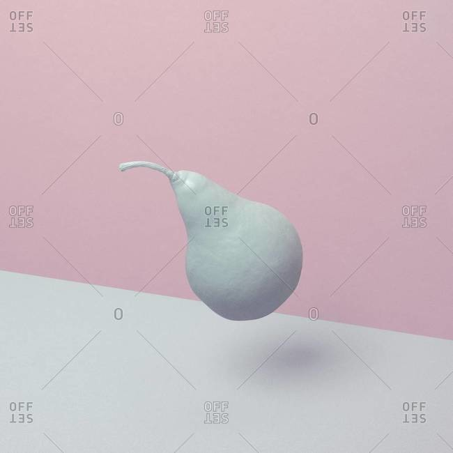 Colorless pear floating over white and pink background