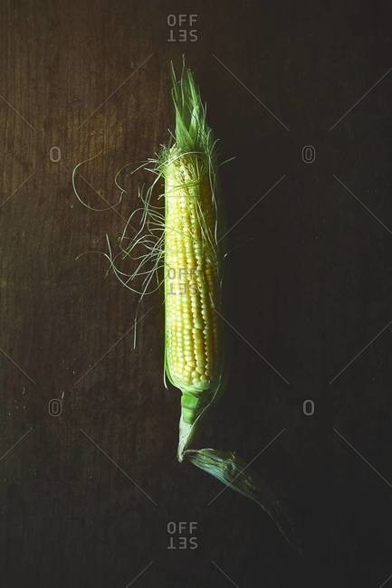 An ear of corn on a wood table