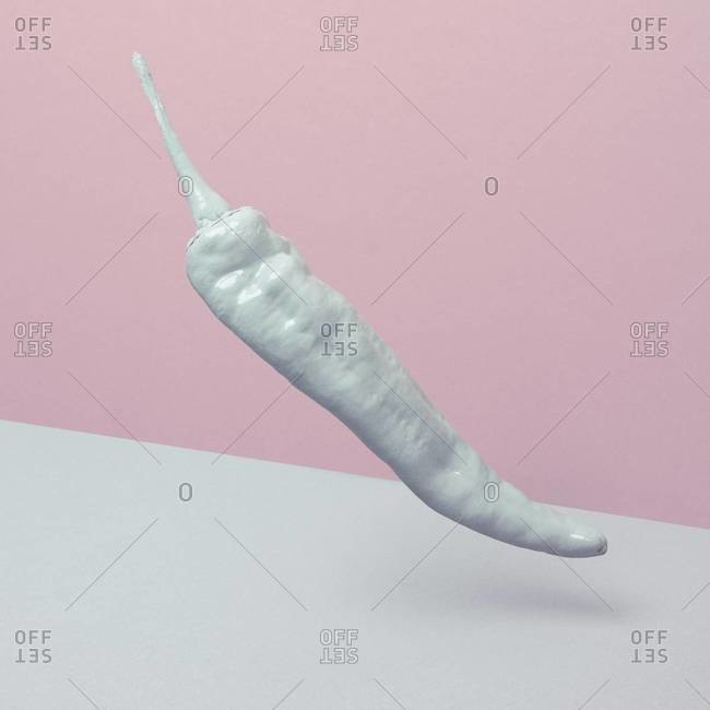 Colorless pepper floating over white and pink background