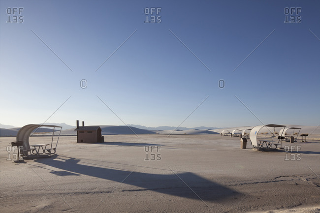 View of a house and picnic shelters in a salt pan desert