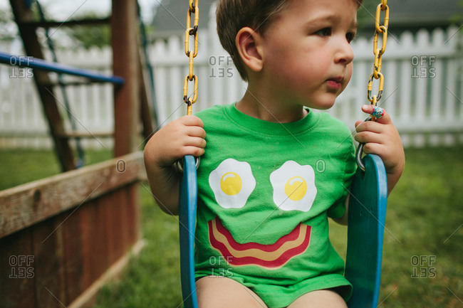 A young boy on a swing stares off to his side.